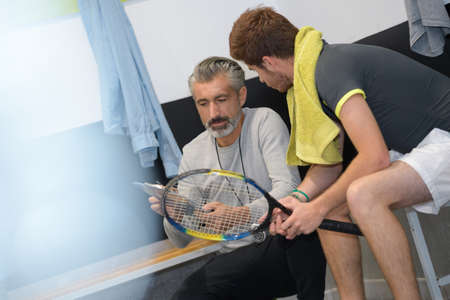 coach advising tennis player in the changing room