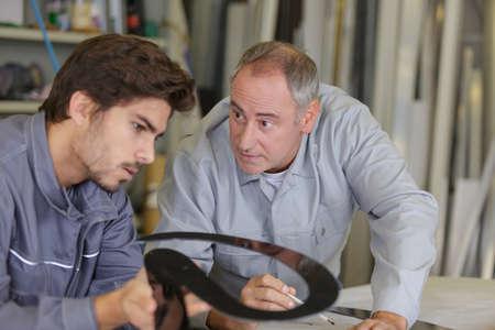 two workmen conferring over paperwork Фото со стока