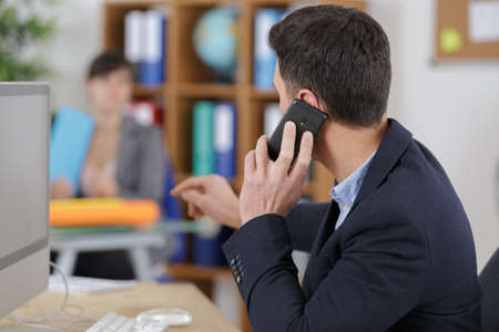 man talking on cell phone and pointing in the office