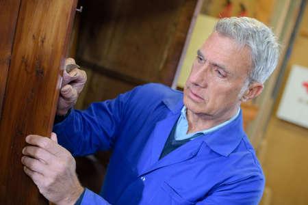 senior craftsman drawing a plan at carpenter workshop