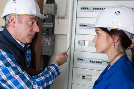 teacher helping female student training to be electrician