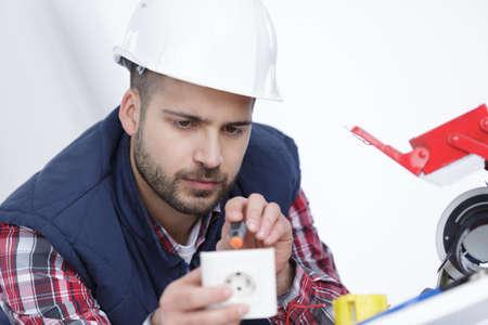 electrician installing socket in new house Фото со стока