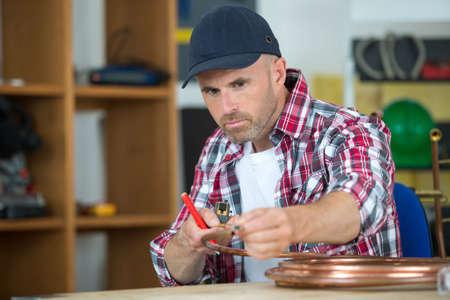 plumber marking copper pipe Фото со стока