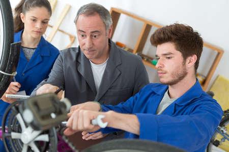 smiling seller repairing bike wheel and chatting to teenage apprentice Фото со стока