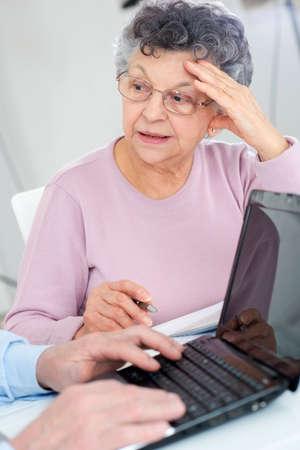 Elderly lady making notes while man uses laptop Фото со стока