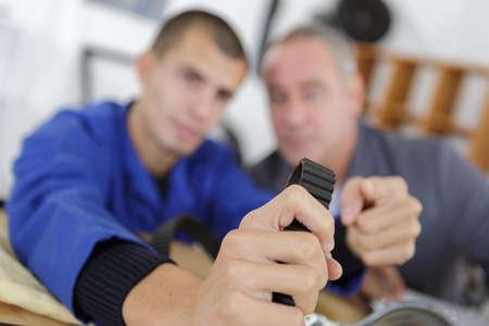 apprentice holding a rubber belt