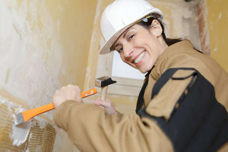 happy female builder with hammer and chisel in the work Фото со стока