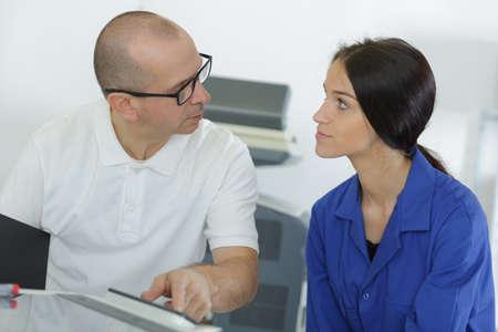 Senior technician talking to female apprentice