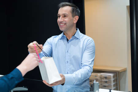 smiling assistant giving purchases to client