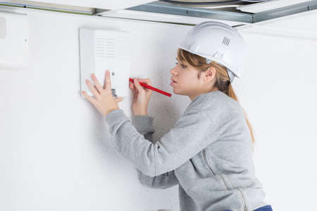 female worker installing smoke detector at home Фото со стока