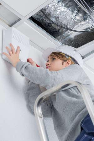 woman fixing ceiling at home Фото со стока