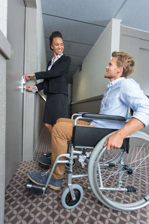 hotel assistant taken care of a young man in wheelchair Фото со стока