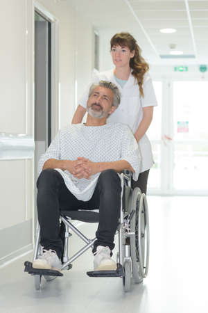 doctor pushing patient on wheelchair in hospital Фото со стока