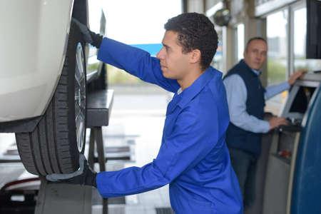 young mechanic inspecting the car wheel Фото со стока