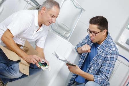 two handyman fixing a washing machine in the kitchen Фото со стока