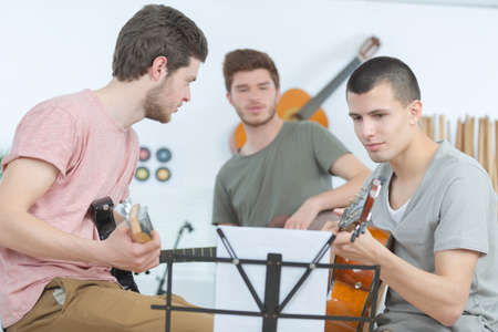 young men playing guitar and composing a song Фото со стока