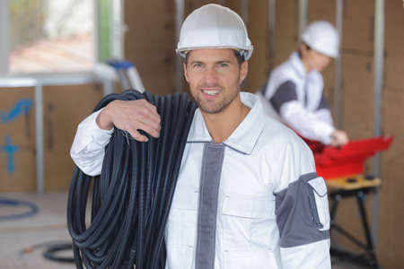 electrician with construction tools and cable