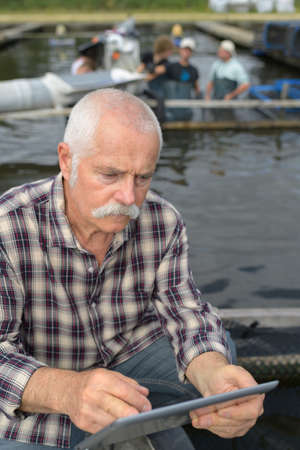 fishery businessman holding a tablet Фото со стока