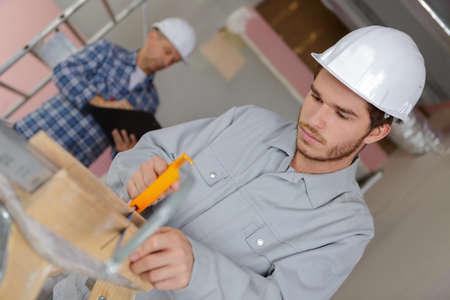 apprentice cutting a plank