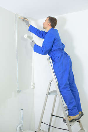 a man painting walls with a brush Фото со стока