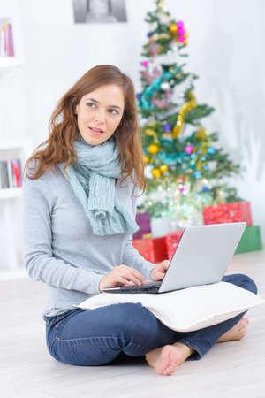 young beautiful woman sitting with laptop near christmas tree Фото со стока