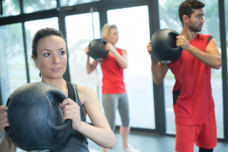 people working with kettle bell in a gym Фото со стока