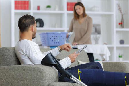 Woman ironing, man on sofa with leg injury