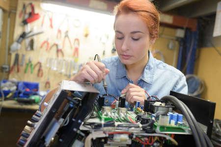 young woman technician repair electronics device toned image