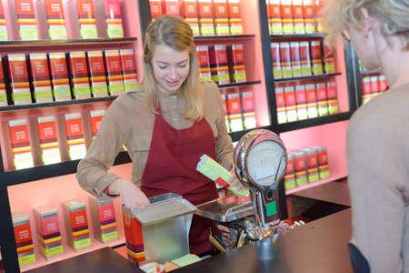 joyful blond woman selling tea by weight in organic shop