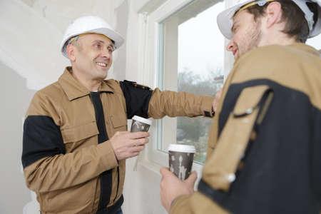 two manual workers enjoying a coffee break Фото со стока