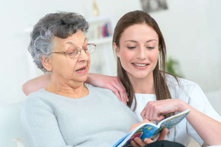 woman and senior woman with book at home