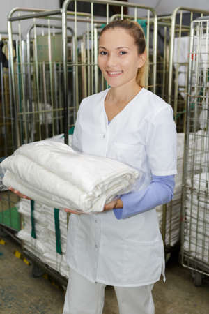 happy female laundry worker at the dry cleaners Stock Photo