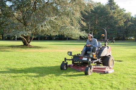 gardener cutting grass of a garden on a lawn mower Stock Photo