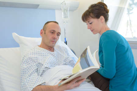 man in hospital with visitor reading a brochure