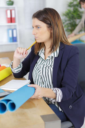concentrated young businesswoman working with blueprint in office Stock Photo