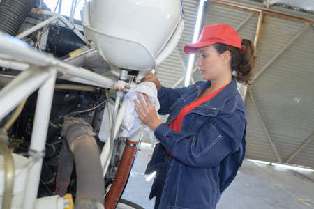 female worker fixing something in the hangar