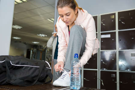 young fitness lady ties laces in gym
