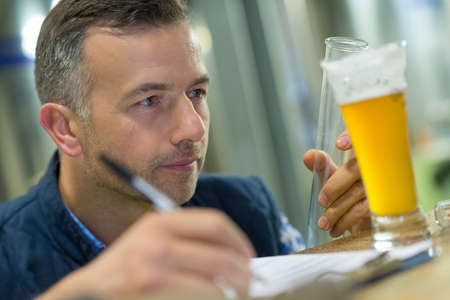 Quality control worker inspecting glass of lager