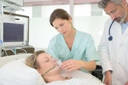 doctors examine female patient in hospital Stock Photo