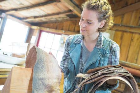 craftswoman inspecting snake skin in her workshop
