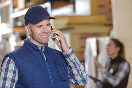 handsome warehouse worker talking by mobile phone