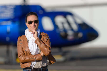 female in front of a helicopter Stock Photo