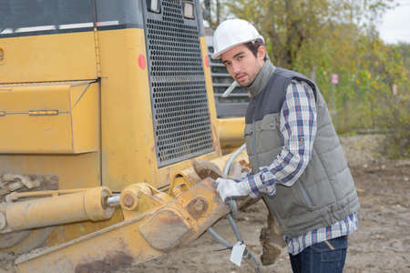 man posing next to a heavy equipment Stock Photo