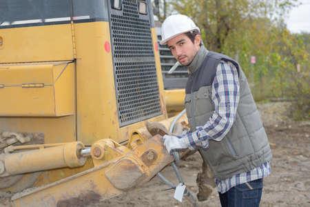 man posing next to a heavy equipment Фото со стока