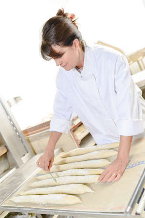 Lady scoring baguettes Stock Photo