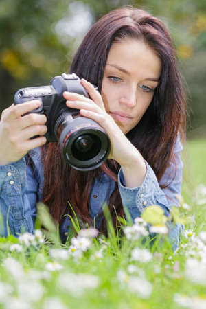 female photographer taking photo of flowering roses in summer day