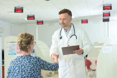 doctor shaking hands with patient in the hospitals waiting room