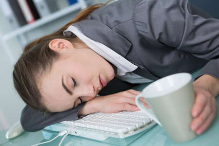 beautiful tired woman sleeping on the keyboard of a laptop
