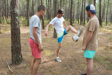 three friends playing football in the forest