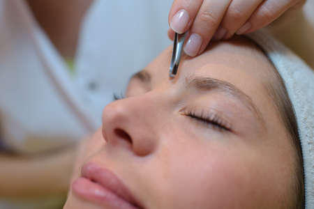 grooming eyebrows in a beauty salon